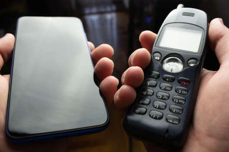 Old and new cell phones in hands on black background