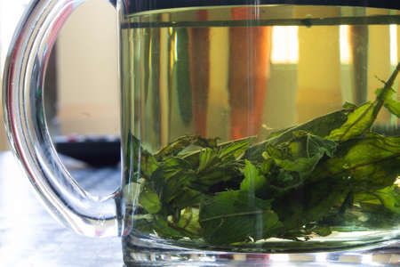Tea with mint in a glass cup close up