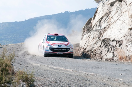 LIMASSOL, CYPRUS - NOVEMBER 7: Driver Burku Cetinkaya (tr) and co-driver Cicek Guney (tr) driving Peugeot 207 S2000 during Rally Cyprus event at Love Cyprus Golden Stage on November 7, 2010 in Limassol, Cyprus.