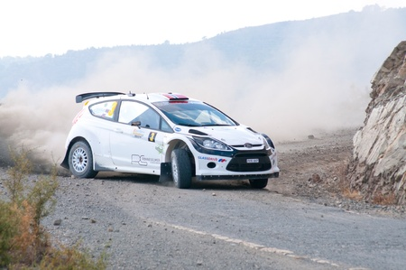 sponsors: LIMASSOL, CYPRUS - NOVEMBER 7: Driver Andreas Mikkelsen (n) and co-driver Ola Floene (n) driving Ford Fiesta S2000 During Rally Cyprus event at Love Cyprus Golden Stage on November 7, 2010 in Limassol, Cyprus.