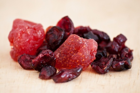 mix of Dried cranberries and strawberries on wooden table photo