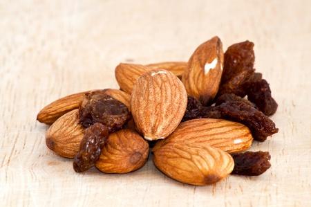 mix of raisinsand almond nut on old wooden table Stock Photo - 9989645