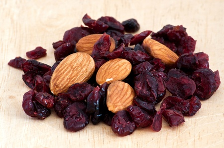 mix of raisinsand almond nut on old wooden table Stock Photo - 9989646