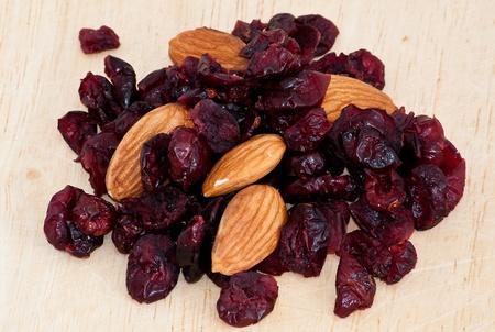 mix of raisinsand almond nut on old wooden table Stock Photo - 9989654