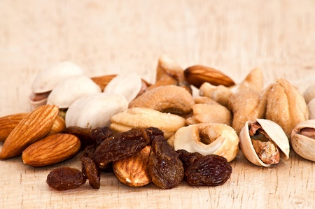 mix of raisins, almond nut, cashew and pistachio on old wooden table Stock Photo - 9989652