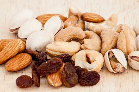 mix of raisins, almond nut, cashew and pistachio on old wooden table Stock Photo - 9989643