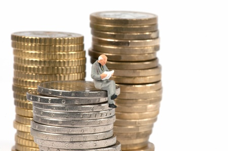 classifieds: Miniature businessman newspaper classifieds, sitting on pile of coins Stock Photo