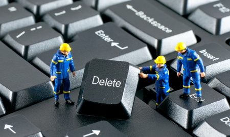 miniature people: Team of construction workers working with DELETE button on a computer keyboard