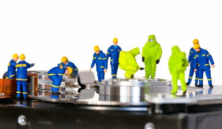 miniature people: Team of technicians repair hard disk. Hard Drive repair concept