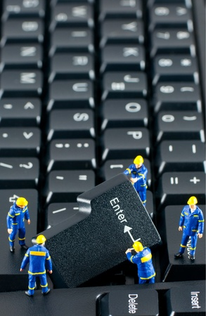 miniature people: Team of construction workers working with ENTER button on a computer keyboard
