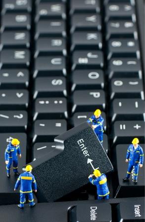 Team van werknemers in de bouw werken met ENTER-toets op een toetsenbord van de computer