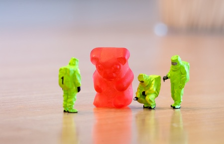 food research: Group of people in protective suit inspecting a jelly bear. Unhealthy food concept Stock Photo