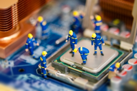 motherboard: Miniature workers repairing computer motherboard Stock Photo