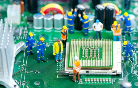 Group of miniature engineers inspecting computer processor photo
