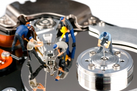 miniature people: Group of construction workers repairing hard disk drive Stock Photo