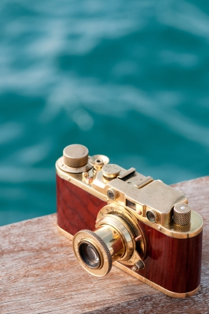 Still life with vintage camera opposite blue sea