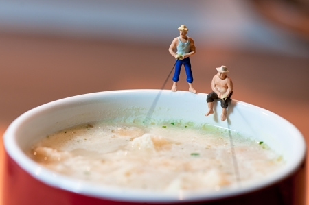 Figurine fishermen fish in a soup mug  Macro photo