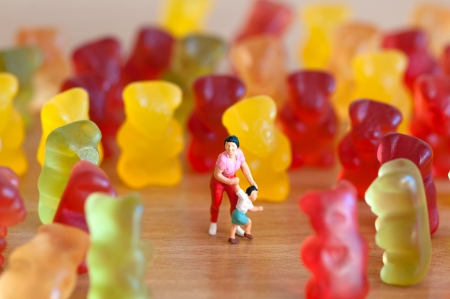 miniature people:  Gummy bear invasion  Harmful  junk food concept