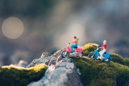 Miniature couple traveling through the countryside on vintage motorcycles at dawn. Macro photography Standard-Bild