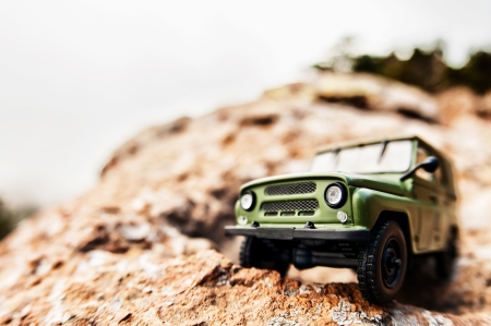 cliff edge: Miniature 4x4 offroad car on the edge of a cliff