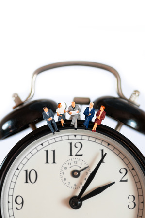 Businesspeople sitting on top of giant clock. Macro photo