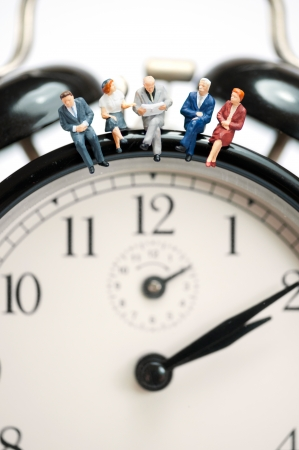 Business team sitting on top of the giant clock. Macro photo