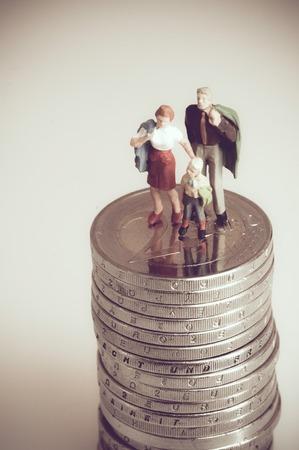 Miniatuur familie op stapel munten. Stockfoto