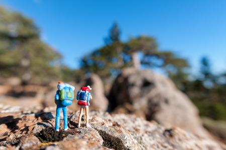 Miniature tourists with backpack. Stock Photo