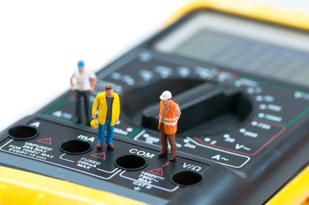 Miniature workers on top of multimeter  Macro photo