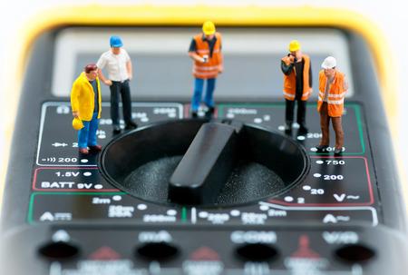 Team van miniatuur werknemers bovenop multimeter Macro foto Stockfoto