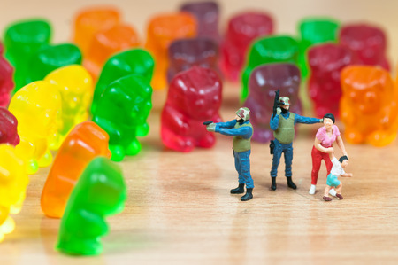green military miniature: Gummy bear invasion  Harmful  junk food concept  Macro photo Stock Photo