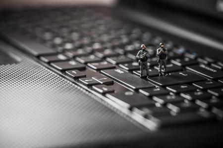 Miniatuur swat team beschermen laptop computer. Technologie-concept Stockfoto
