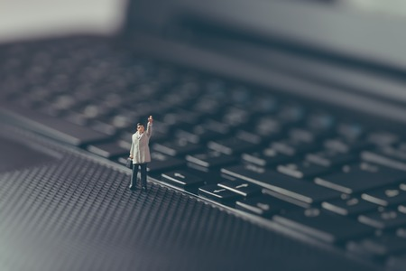 Miniature businessman waving on top of the laptop. Business concept. Macro photo photo