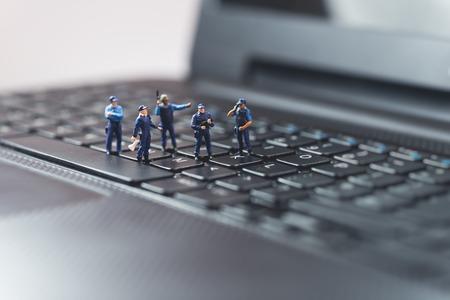 Miniature police squad protecting laptop computer. Technology concept Standard-Bild