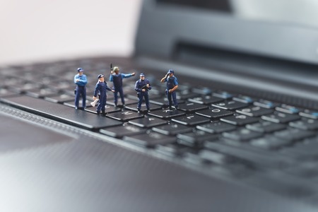 Miniature police squad protecting laptop computer. Technology concept Stockfoto