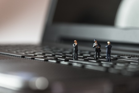 Miniature business people standing on laptop keyboard photo