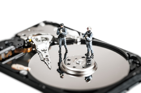 Miniature soldiers protecting computer hard drive. Technology concept. photo