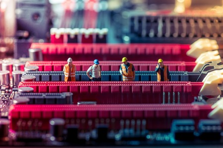 Miniature engineers repairing circuit board. Technology concept photo