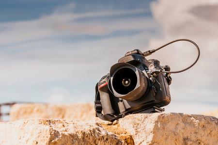 microstock: Professional digital camera on top of the stone block. Close up photo. Stock Photo