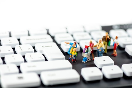 コンピューターのキーボードを見てやさしいミニチュア家族。技術コンセプト。マクロ写真