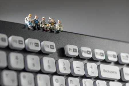 klawiatury: Miniaturowe robotnicy siedzą na górze klawiatury. koncepcji technologii. Fotografia makro