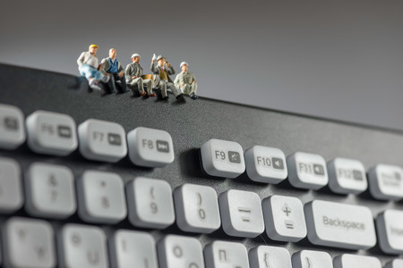 Miniature workers sitting on top of keyboard. Technology concept. Macro photo Foto de archivo