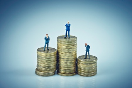 Financial concept. Business people standing on coins piles. Macro photo Standard-Bild