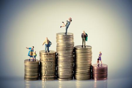 pieniądze: Faily koncepcja budżetu. Miniaturowe rodziny na monet stos. Fotografia makro