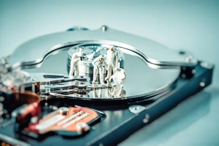 harddisc: Group of criminalists inspecting hard drive. Technology concept. Macro photo.