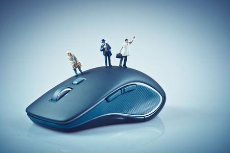 miniature: Miniature people on top of computer mouse. Business concept. Macro photo