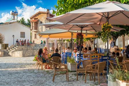 OMODOS, Zypern - 4. Oktober 2015: Straßen Cafés mit Touristen am 4. Oktober in Omodos Dorf, Limassol District. Editorial