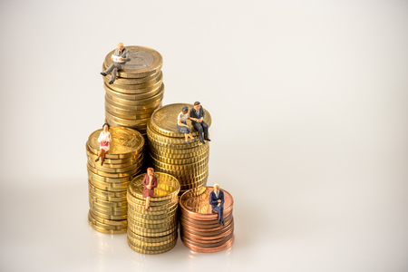 Various businesspeople sitting on money coin piles. Macro photo