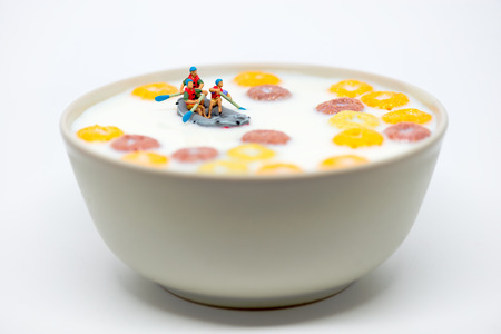 miniature: Rafting in a bowl of colorful cereal with milk. Healthy breakfast concept. Macro photo