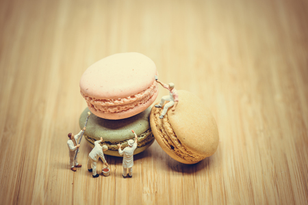macro   photo: Group of miniature painters coloring macaroon. Color tone tuned. Macro photo